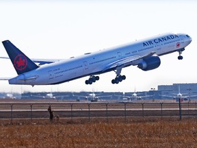 An Air Canada Boeing 777 takes off at the Calgary International Airport while WestJet Boeing 737 are lined up in storage in the distance on Tuesday, March 23, 2021.