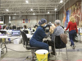 A health-care worker administers a COVID-19 vaccine at the Bill Durnan Arena vaccination site in Montreal, on March 10.