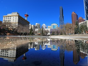 The downtown Calgary skyline is reflected in a pool of water at Olympic Plaza on Monday, April 26, 2021. Calgary city council is considering a 10-year plan to revitalize the downtown core.