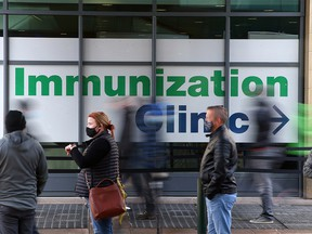 People are lining up to receive their COVID-19 vaccinations outside the immunization clinic at the Telus Convention Centre on Stephen Avenue, Thursday, April 22, 2021.