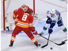 Calgary Flames goaltender Jacob Markstrom and defencemen Chris Tanev guard the net from Vancouver Canucks forward Nils Hoglander during the Calgary Flames NHL home opener on Saturday, January 16, 2021.   Gavin Young/Postmedia