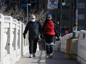 Jason Kozar and Sora Han cross the 10th Street Bridge into Kensington on Thursday, April 8, 2021.