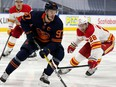 The Edmonton Oilers' Connor McDavid (97) battles the Calgary Flames' Elias Lindholm (28) during third period NHL action at Rogers Place, in Edmonton Thursday April 29, 2021. The Flames won 3-1. Photo by David Bloom