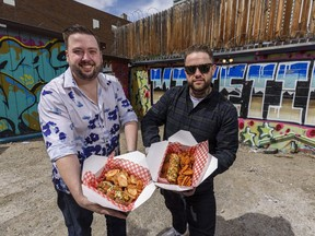 Ray Burton, left, general manager, and Alex Durant, Chef/hot dog enthusiast, with Lost Dogs hot dogs pose for a photo in a back alley in Beltline on Thursday, April 29, 2021.  Burton is holding The Chinook Dog with Malt Vinegar Potato Chips and Durant is holding The Prince's Island Dog with Waffle Fries. Azin Ghaffari/Postmedia