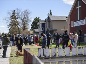 A group of community members have gathered on the lawn neighbouring Street Church, which is holding a gathering despite COVID-19 restrictions, on Saturday, May 1, 2021. The neighbours of the church say they feel unsafe and harassed by the churchgoers and their pastor Artur Pawlowski.