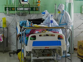 In this picture taken on May 5, 2021, health workers wearing personal protective equipment suits attend to a COVID-19 patient inside the Intensive Care Unit (ICU) of the Teerthanker Mahaveer University (TMU) hospital in Moradabad, India.