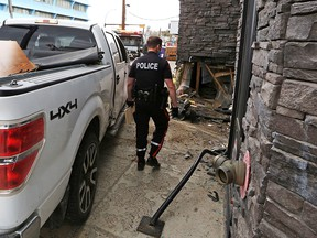 A pickup truck is extricated from a wall on The Pint Public House on 17th Avenue S.W. on Thursday, May 13, 2021. A driver and passenger fled the scene after the collision.