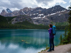 A hiker looks at Lake O'Hara, located in Yoho National Park, in this undated handout image.