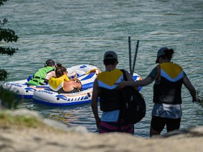 People spend the extremely hot morning on and long the Bow River in Bowness Park on Thursday, June 3, 2021.