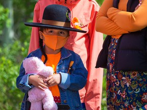 Charly Dodginghorse, 4, holds her teddy bear before silently marching with her family and other Tsuut'ina people on their reservation, Monday, June 7, 2021. The march was in memory of the 215 unmarked graves found at a residential school in Kamloops.