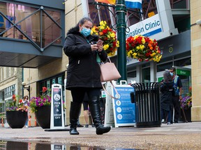 Calgarians walk past the downtown COVID-19 vaccination clinic on Thursday, June 24, 2021.
