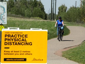 A woman is seen on her bicycle in Fish Creek Park during a hot day. Thursday, June 3, 2021.
