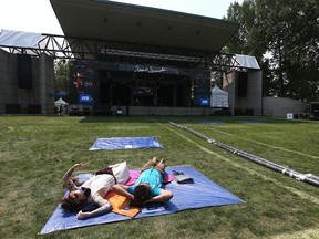 Stephanie Mom, left, and Jordan Schroter wait for performances to begin at the Calgary Folk Music Festival in downtown Calgary on Sunday, July 25, 2021.
