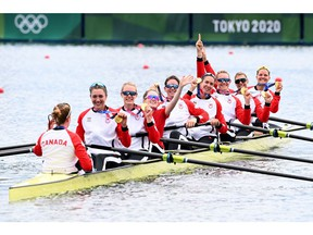 Canada's gold medallists (from right to left) Lisa Roman, Kasia Gruchalla-Wesierski, Christine Roper, Susanne Grainger, Andrea Proske, Madison Mailey, Sydney Payne Avalon Wasteneys and coxswain Kristen Kit pose in their boat following the women's eight final during the Tokyo 2020 Olympic Games at the Sea Forest Waterway in Tokyo on July 30, 2021. (Photo by Charly TRIBALLEAU / AFP)