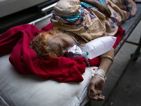 A COVID-19 patient waits to be transferred to a different hospital because the ICU at the hospital she was admitted to was full, on July 25, 2021 in Dhaka, Bangladesh.