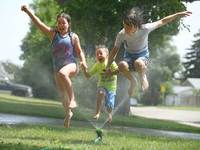 Left to right: Mimi, Niels and Aksel Chapman beat the heat by running through a sprinkler at their Highwood home on July 9, 2021.