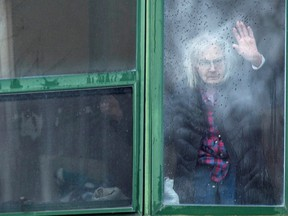 A resident waves from her window at Residence Herron, site of a deadly COVID-19 outbreak in April, 2020, in Laval, Que.