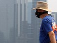 A man wearing a mask is seen walking along McHugh Bluff with office towers in the background as wildfire smoke continues to effect air quality in Calgary on Wednesday, Aug. 4, 2021.
