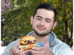 Farbod Jahanshah enjoys a burger from Alumni Sandwiches along 17th Avenue S.W. Jahanshah put his business school skills to the test by creating a rating system of Calgary's dowtown burger joints. Brendan Miller/Postmedia