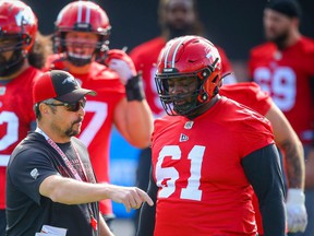 Stampeders offensive coordinator & offensive line coach Pat DelMonaco and Ucambre Williams chat during practice in Calgary earlier this month.