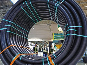 Workers check out a spool of pipe on display at the FlexSteel booth at the Global Petroleum Show in Calgary in 2018. The annual event — now called the Global Energy Show — has been postponed to 2022 due to rising COVID numbers.