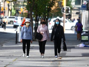 People are seen wearing masks while walking along 8th Ave. S.W. Tuesday, September 7, 2021.