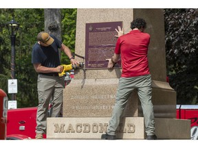 Workers remove a plaque on the monument that held the statue of Sir John A. Macdonald in Kingston, Ontario on Friday June 18, 2021. The statue will be removed from a park in his hometown of Kingston while his name will be taken off a local school.  Kingston's city council voted this week to take the statue from City Park, place it temporarily in storage, and eventually put it up in Kingston Cataraqui Cemetery where Canada's first prime minister is buried.