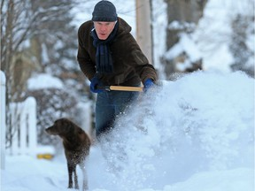 Chris Edison clears snow from a sidewalk in Crescent Heights Wednesday December 20, 2017. A winter storm hit Calgary overnight leaving over 20 centimetres in parts of the city. Gavin Young/Postmedia  Postmedia Calgary