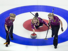 Skip Chelsea Carey, from Calgary, Alta. throws a rock as lead Laine Peters and second Jocelyn Peterman prepare to sweep during the Olympic curling trials Wednesday December 6, 2017 in Ottawa. THE CANADIAN PRESS/Adrian Wyld ORG XMIT: ajw110