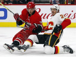 Carolina Hurricanes' Elias Lindholm collides with Calgary Flames' Travis Hamonic during the second period of an NHL hockey game, Sunday, Jan. 14, 2018, in Raleigh, N.C.