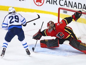 Calgary Flames goaltender Mike Smith stops this shot by Patrik Laine during a shoot-out in NHL action at the Scotiabank Saddleome in Calgary on Saturday January 20, 2018.