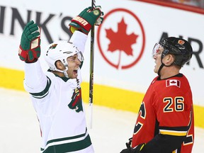 Jason Zucker celebrates the Wild's game-winning goal in front of Flames Michael Stone at the Saddledome on Oct. 21, 2017.