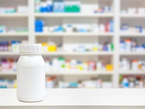 In this stock photo, a blank white medicine bottle sits on the counter of a pharmacy.