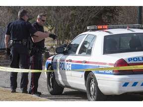CALGARY, AB -- Officers talk outside the cruiser holding their suspect after an officer-involved shooting in Stanley Park on March 20, 2016. Crystal Schick/Crystal Schic