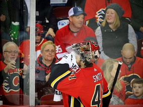 Calgary Flames goaltender Mike Smith wipes his face during a break in play at the Scotiabank Saddledome in Calgary on Sunday, March 11, 2018. (Al Charest/Postmedia)