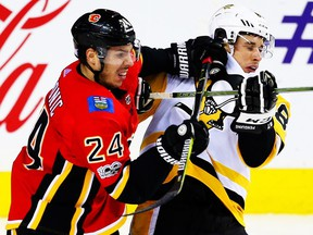 Calgary Flames Travis Hamonic battles against Sidney Crosby of the Pittsburgh Penguins during NHL hockey at the Scotiabank Saddledome in Calgary on Thursday, Nov. 2, 2017.