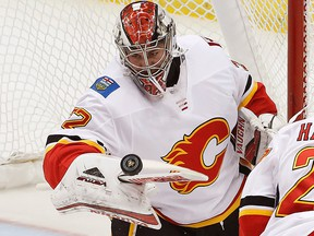 Calgary Flames goaltender Jon Gillies (32) deflects a shot with his stick in the first period of an NHL hockey game against the Pittsburgh Penguins in Pittsburgh, Monday, March 5, 2018.