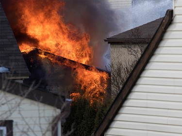 A garage where a possible suspect was hidden burns after a police officer was shot in Abbeydale in Calgary on Tuesday March 27, 2018.
