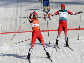 Canada's Brian McKeever (right) and guide Russell Kennedy celebrate after winning the men's 1.5k sprint classic, visually impaired, cross-country skiing at the 2018 Winter Paralympics in Pyeongchang, South Korea, Wednesday, March 14, 2018.