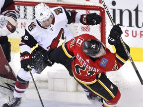 Calgary Flames' Garnet Hathaway (right) is knocked down by Arizona Coyotes' Trevor Murphy in front of the Arizona net during second period NHL action in Calgary, Alta., Tuesday, April 3, 2018.