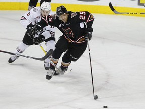 Crystal Schick/ Independent CALGARY, AB -- Calgary Hitmen Aaron Hyman fights off Red Deer Rebels Grayson Pawlenchuk during game action in Calgary, on December 9, 2016. -- (Crystal Schick/Independent)