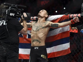 Max Holloway, stands in front of the state flag of Hawaii, as he prepares to fight Jose Aldo of Brazil during a UFC 218 featherweight mixed martial arts bout, Sunday, Dec. 3, 2017, in Detroit.