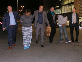 Yu Chieh Liao, left, and Tewodros Mutugeta Kebede are taken into custody in Calgary on Oct. 10, 2017.