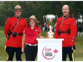 REGINA, CANADA - AUGUST 26:  Brooke Henderson of Canada with the champions trophy and Canadian Mounties following the final round of the CP Women's Open at the Wascana Country Club on August 26, 2018 in Regina, Canada.
