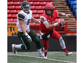 Calgary, AB - September 29, 2018. University of Calgary quarterback #12 Adam Sinagra escapes pressure from University of Saskatchewan Huskies # 91 Riley Pickett. The  Dinos defeated the Huskies 33-13 Saturday afternoon at McMahon Stadium during Canada West football action.  Photo by David Moll / Dinos Digital Media
