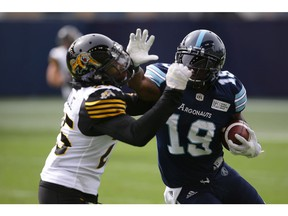 Toronto Argonauts wide receiver S.J. Green (19) hits Hamilton Tiger-Cats defensive back Terrence Frederick (25) with a stiff arm as he runs up field with the ball during second half CFL football action, in Toronto, Saturday, Sept. 8, 2018.