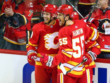 The Calgary Flames Elias Lindholm and Noah Hanifin celebrate with Johnny Gaudreau after his career 100th goal during NHL action against the Boston Bruins at the Scotiabank Saddledome in Calgary on Wednesday October 17, 2018.