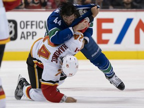 Erik Gudbranson of the Vancouver Canucks knocks down Flames defenceman Travis Hamonic on Oct. 3, 2018 at Rogers Arena in Vancouver.
