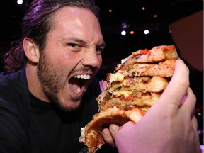 Calgary Stampeders Alex Singleton feasts during The 16th Annual 2018 Eric Francis Pizza Pigout in support ofKidSport CalgaryYou Can PlayandKids Cancer Care Foundation of Alberta at Cowby's Dance Hall in Calgary on Thursday October 18, 2018. Darren Makowichuk/Postmedia