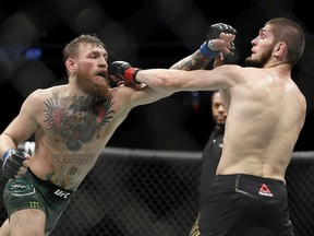 Conor McGregor, left, and Khabib Nurmagomedov throw punches during a lightweight title mixed martial arts bout at UFC 229 in Las Vegas, Saturday, Oct. 6, 2018.
